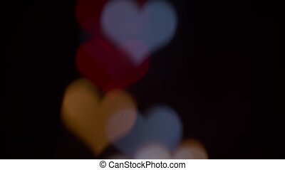Several refocusing flashing colorful hearts on a black background. Blurry bokeh