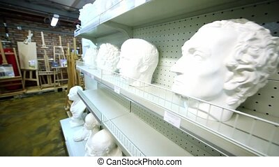 Several sculpture heads are on shelves in store
