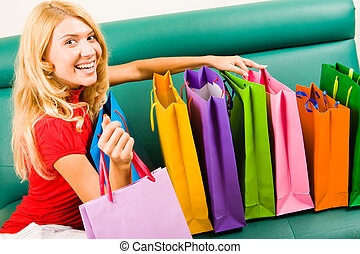 Several shoppingbags - Portrait of smiling blonde sitting on...