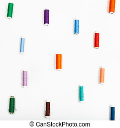 several spools of sewing thread on white