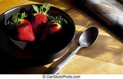 Strawberries in Black Bowl on Wooden Surface