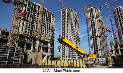 Several tall buildings under construction with cranes