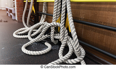 Several thick white ropes on the floor in a gym