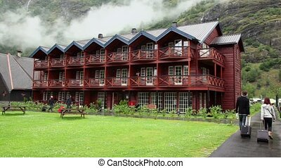 Several tourists walk near wooden hotel under mountain