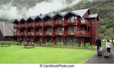 Several tourists walk near wooden hotel under mountain