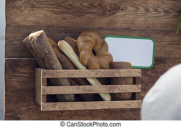 Several types of bread in a wooden display case.