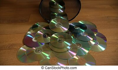 Several useless digital discs falling out of the dustbin.