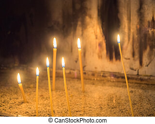 Several wax candles lighted in a dark room.