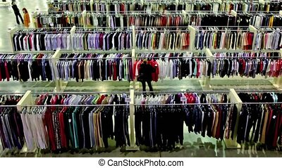 Several women watch goods among lot of clothes in large shop