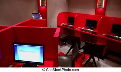Several workplaces in empty internet cafe with red...