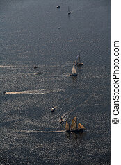 Several yachts and sailboats go to sea under sail. View from...