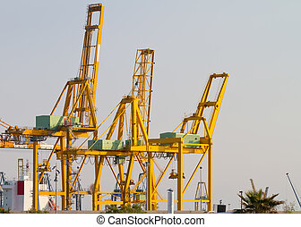 three big yellow cranes and blue sky