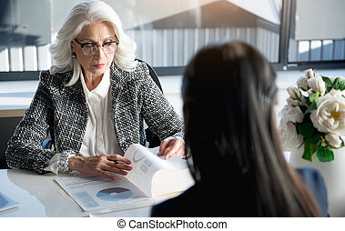 Severe old woman working with her colleague