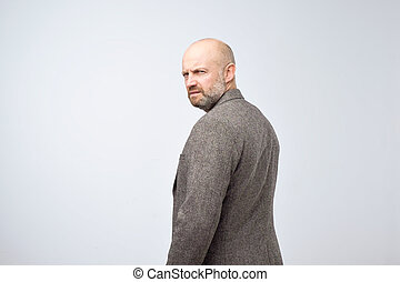 Severe strict man with beard in casual suit turning back