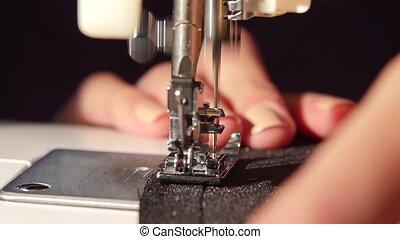 Sew a black cloth. Slow motion - Sew a black cloth, woman...