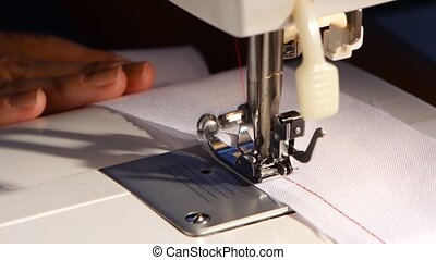 Sew a red thread on white cloth. Close up