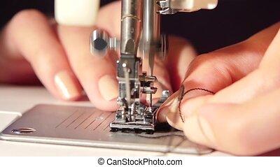 Sew black fabric. Slow motion - Sew black fabric, woman sews...