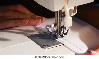 Sew on a white cloth with red thread. Slow motion