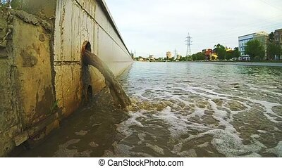 Sewage Pipe Discharging Into The River. The drain carries sewage