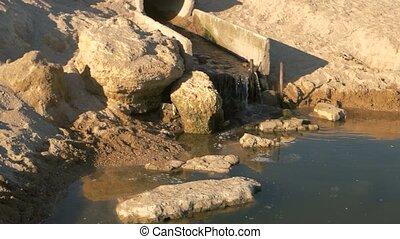 Sewage pipe near the seashore. Dark dirty water. Pollution...