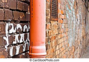 Sewage pipe on brick abandoned wall
