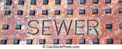 Sewer lid. -  Rusty sewer lid on concrete pavement outside.