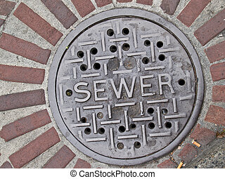Sewer manhole lid in street, brick surround.