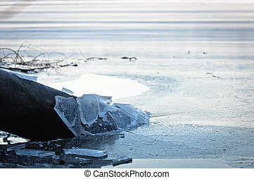 Sewer pipe frozen into water at winter