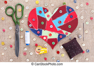 Sewing accessories and fabric scraps heart on fabric texture...