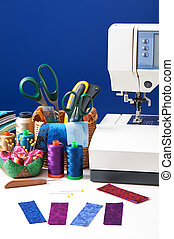 Sewing accessories in a basket and spools of threads next to sewing machine