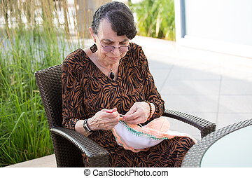 Sewing as a hobby - Closeup portrait, grandmother sitting ...