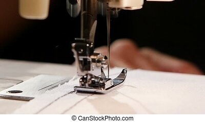 Sewing black thread on white fabric, woman sews on the sewing machine, the needle pierces the fabric, sewing, sewing machine, sewing on the fabric, profession, clothing production, sewing needle and thread, slow motion