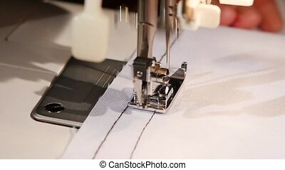 Sewing black thread on white fabric. Slow motion