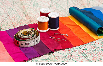 Bobbins of thread and tape measure on paper sewing pattern.