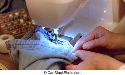 Sewing denim jeans. Repair jeans by sewing machine. Slow...