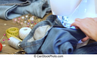 Sewing denim jeans with sewing machine. Repair jeans by...