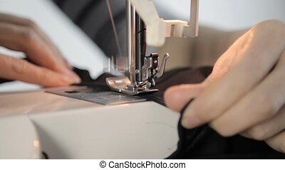 sewing machine and woman hands, dressmaker supporting a cloth.