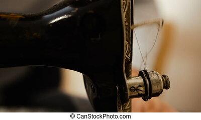 Sewing machine. Elderly hands sew on a sewing machine.