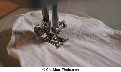 Sewing Machine Needle in Motion. A Tailor Sews Homemade Face Mask of Fabric
