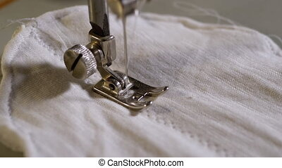 Sewing Machine Needle in Slow Motion. A Tailor Sews Homemade Face Mask of Fabric