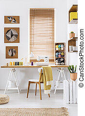 Sewing machine on a wooden desk by the window in a scandi crafts room interior with white walls and yarn. Real photo.