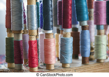 Sewing multicolored threads of soft pastel vintage colors on spools. Sewing tailor related accessories.