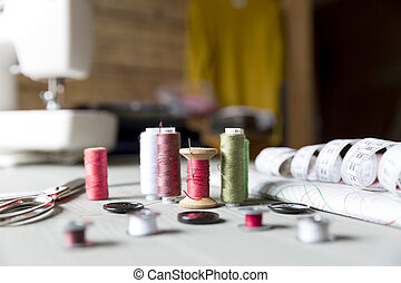 sewing, sewing on the sewing machine, sewing supplies, colored sewing threads, centimeter, tailors scissors, buttons