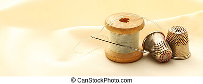 Sewing thimbles, bobbin and needle on silk cloth