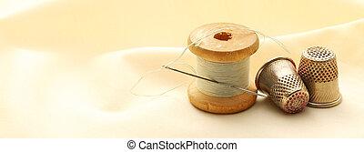 Sewing thimbles, bobbin and needle on silk cloth
