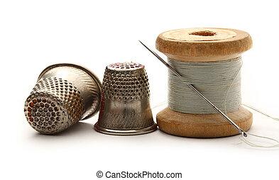 Sewing thimbles, bobbin and needle