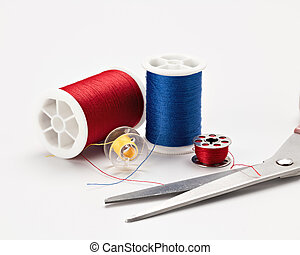 sewing thread and a pair of scissors of different colors