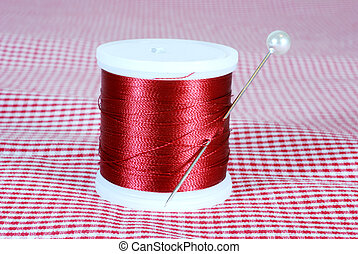 Sewing thread and needle on red and white fabric.