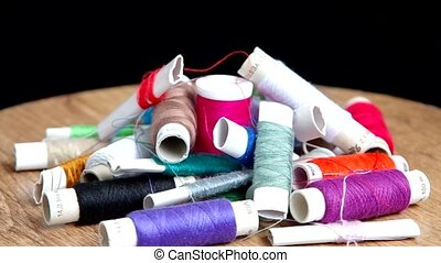 Sewing thread - Colorful sewing thread are rotated on the ...