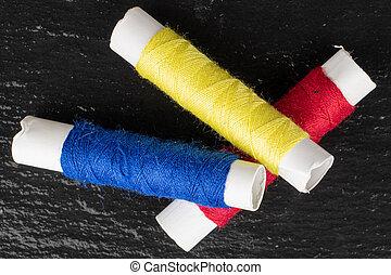 Sewing thread spool on grey stone